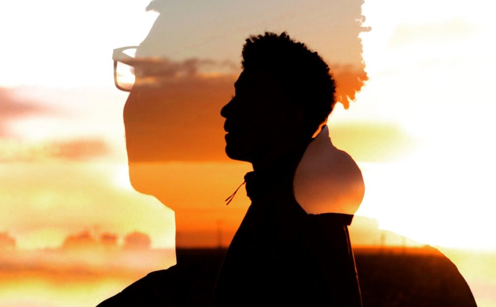 A silhouette of a young man's head against a sunset