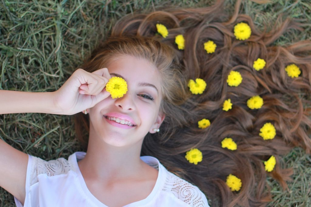 a girl lying on the grass with flowers in her hair