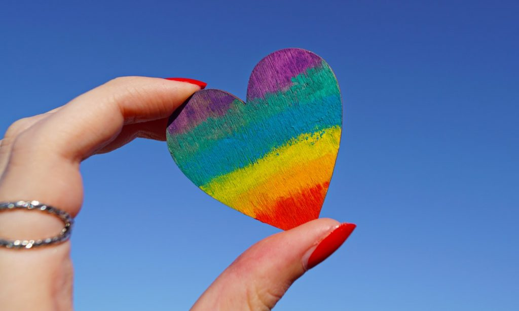 a person holding a rainbow-coloured heart