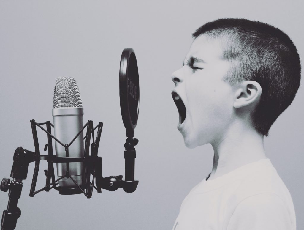 a boy shouting into a microphone